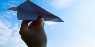 Hand holding paper plane in blue sky